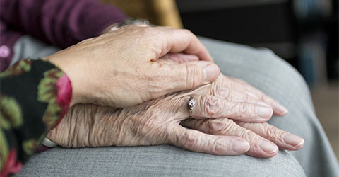 A person holds the hand of an elderly person on a visit to help them improve their health and welllbeing