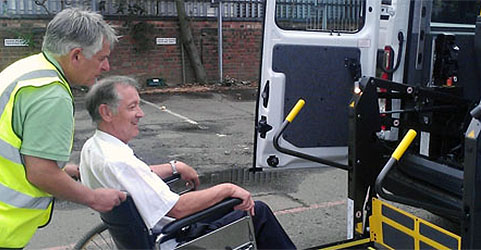 Driver helping a wheelchair user get into a minibus