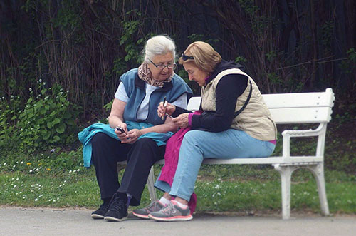Two women friends sitting on a park bench talking to each other