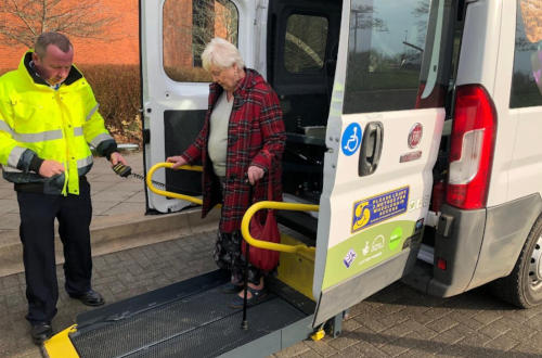 Driver help elderly woman get off a minibus tail lift